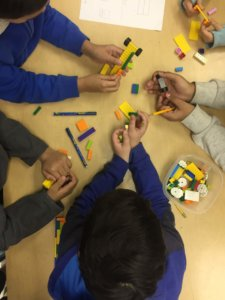 Students work at a table with Legos.