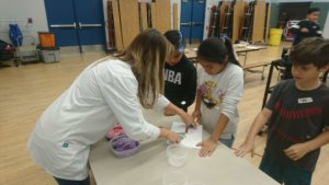 An instructors helps a student group with their plant card during the photosynthesis game.