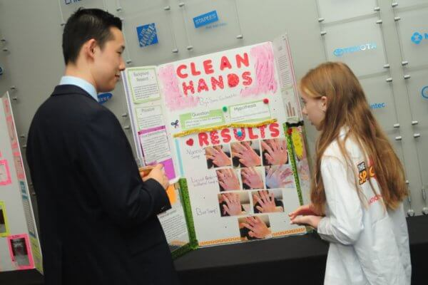 Student showing her science fair board at the gala to an adult.