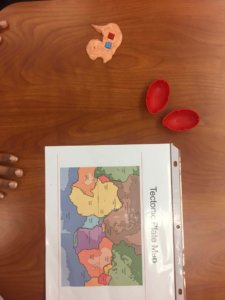 Silly putty with small tiles are shown with a map of the tectonic plates.