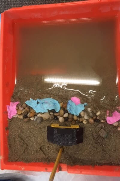 A model beach is shown in a paint tray as students build an erosion barrier.