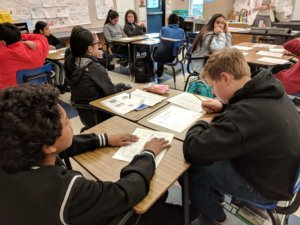 Students work on worksheets at their desks.