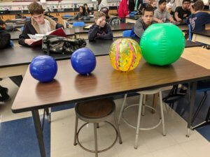 Students look at varying size inflated beach balls representing different planets.