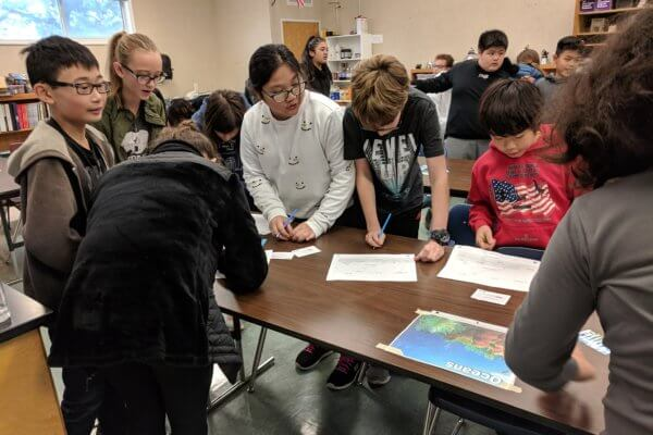 Students work at a table during the Water Cycle game.