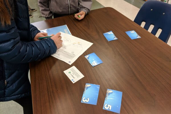 Students fill in a worksheet at one of the water cycle game stations.