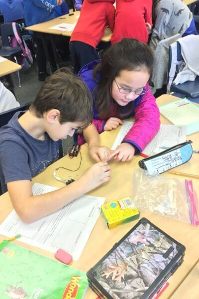 Two students connect wires in a circuit.