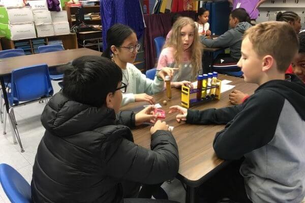 Student investigate vials of liquid observing viscosity.