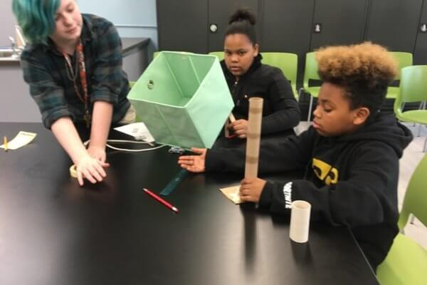 Students work with tubes and the cloth cube to build a Rube Goldberg device.