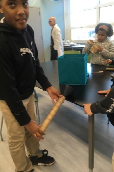 Students use a funnel and a tube as they build a Rube Goldberg device.