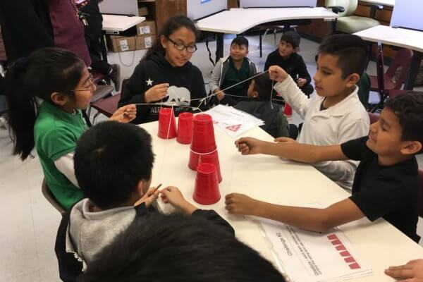 Students use a string tool to stack solo cups.
