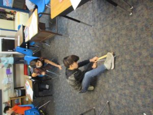 Students measure a rope on the floor with a ruler.