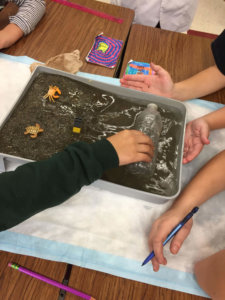 Students Create a model storm in their model beach.