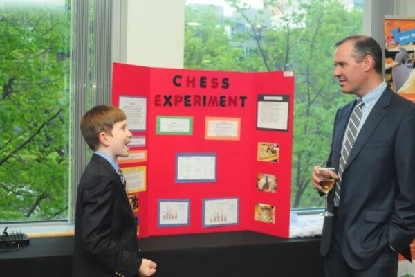 Student showing his science fair board at the gala to an adult.
