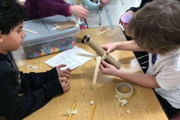 Students work at a table with tape, tubes, cardboard and cups to make a Rube Goldberg device.