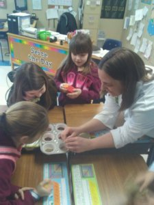 An instructor shows soil samples to students.