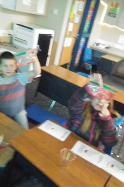 Students hold up plastic bags with a solution as part of extracting DNA.