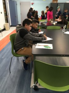Students work at a table filling in a worksheet.