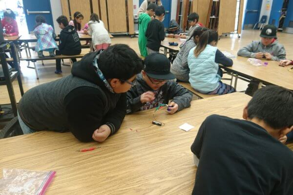 Students build circuits and test materials to see which are conductors.