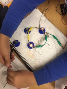 Students create circuits to light up a bulb.