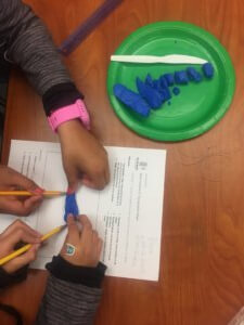 Students trace playdough on a worksheet to make a topographic map.
