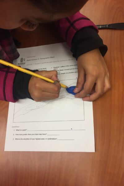 Student traces playdough on a worksheet.