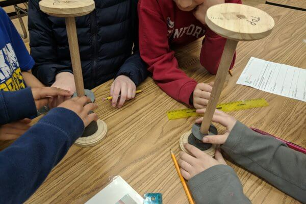 Students experiment with wooden contraptions that have magnets attached to them.