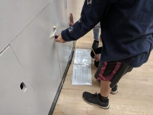 Students measure a ball height with a ruler taped to the wall.