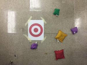 Bean bags land near a target on the floor.