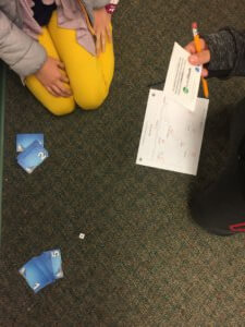 Students roll die and read cards as part of the Water Cycle game.