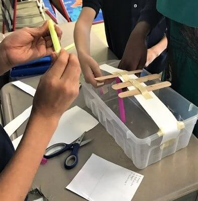 Students building a bridge in a plastic container.