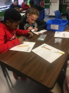 Two students look at their fingerprints with magnifying glasses.