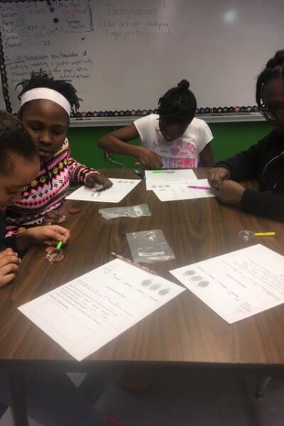 Students working at a table looking at their fingerprints in clay with magnifying glasses.