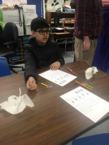 A student sitting at a table with a worksheet, pencils and magnifying glasses.