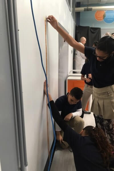 Students use a measuring tape against the wall.