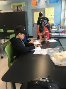 Students work at a table to investigate magnets.