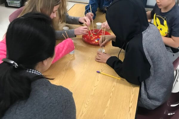 Students use chopsticks to fish for wooden fish in a plastic plate pond.