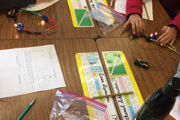 Students build circuits to turn on a light.