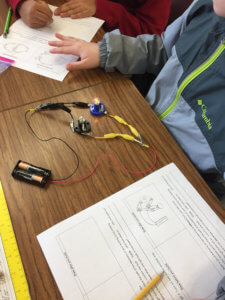 Students build a circuit to power a small lamp.