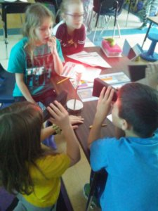 Students look through spectrometers at a light bulb.