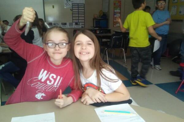 A student holds up a tube while working with a partner.