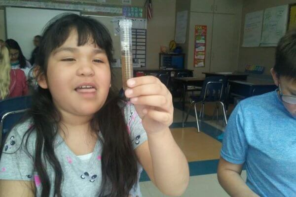 Student holds up a test tube with a brown liquid in it.