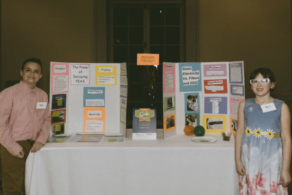 Two students show their science fair projects at the STEM gala.