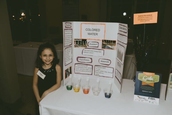 A student shows her science fair project at the STEM gala.