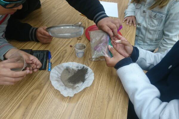 Students use tools to separate a mixture.