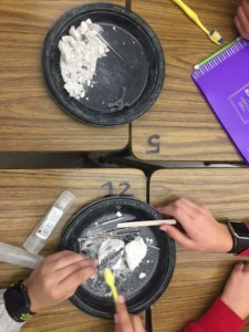 Students use tools to uncover a model fossil.