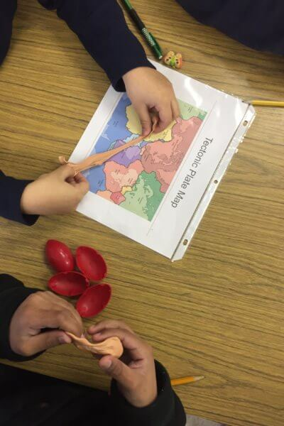 Students use silly putty to model tectonic plate movements.