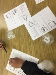 Cups with dry ice and worksheets are shown.