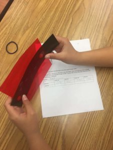 A student holds a red filter to look at how it effects differnt colors of paint on a black background.