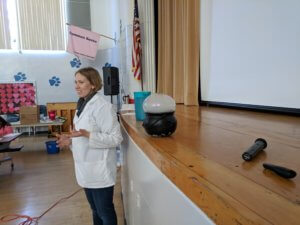 An instructor stands in front of a cauldron with a dry ice bubble.