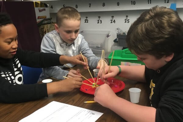 Students use chopsticks to fish for wooden fish.